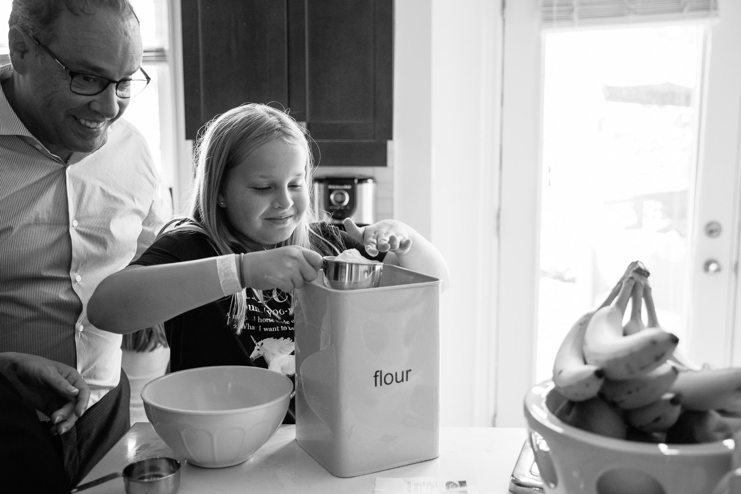 father leaning over 10 year old daughter's shoulder as she measures flour to make pancakes for family brunch - Stouffville Lifestyle Photos