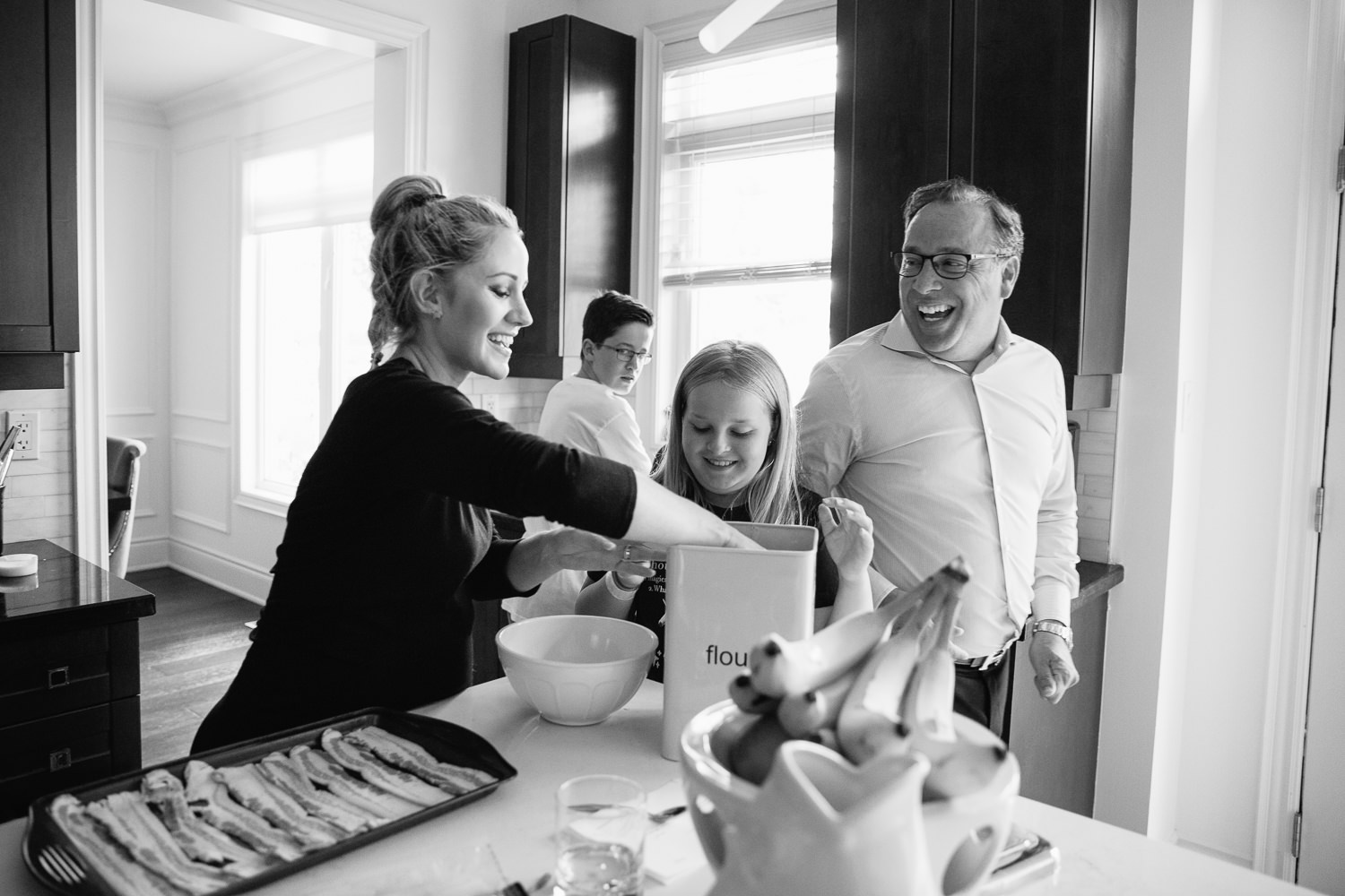 family laughing together in kitchen, mom and 10 year old daughter scooping flour as dad walks by, 13 year old boy in background - Barrie Lifestyle Photos