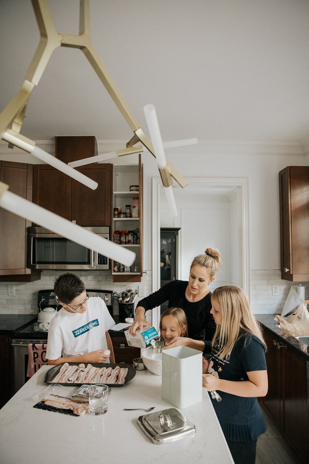 3 children standing at kitchen island with mom helping to mix pancake batter for family brunch, 8 and 10 year old girls, 13 year old boy - GTA Lifestyle Photos