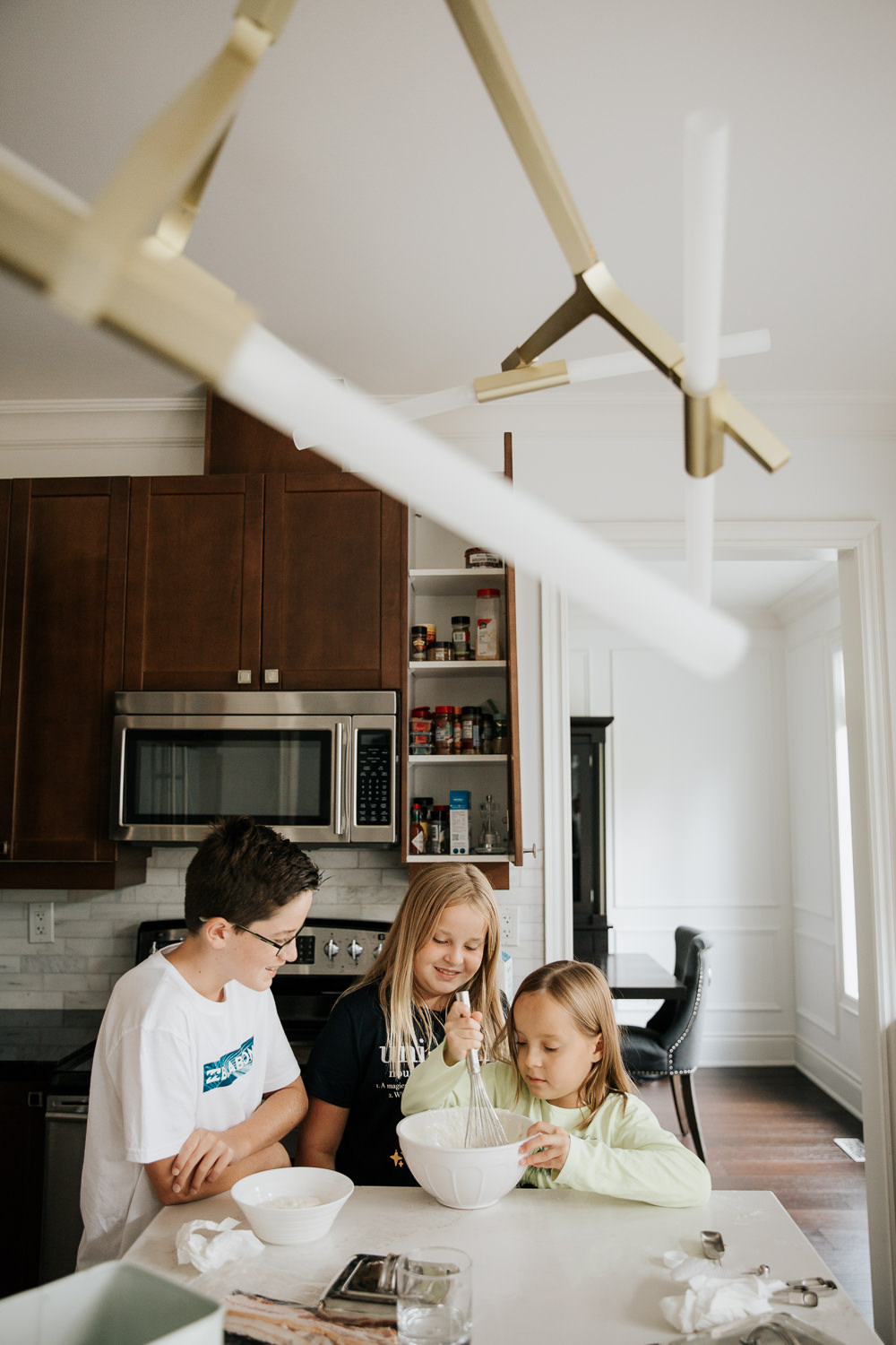 3 children standing at kitchen island mixing pancake batter for family brunch, 8 and 10 year old girls, 13 year old boy - York Region Lifestyle Photos