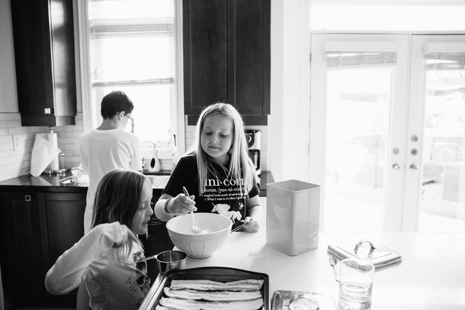 8 and 10 year old sisters standing at kitchen island mixing pancake batter for family brunch, 13 year old brother at sink behind them -Stouffville Lifestyle Photography