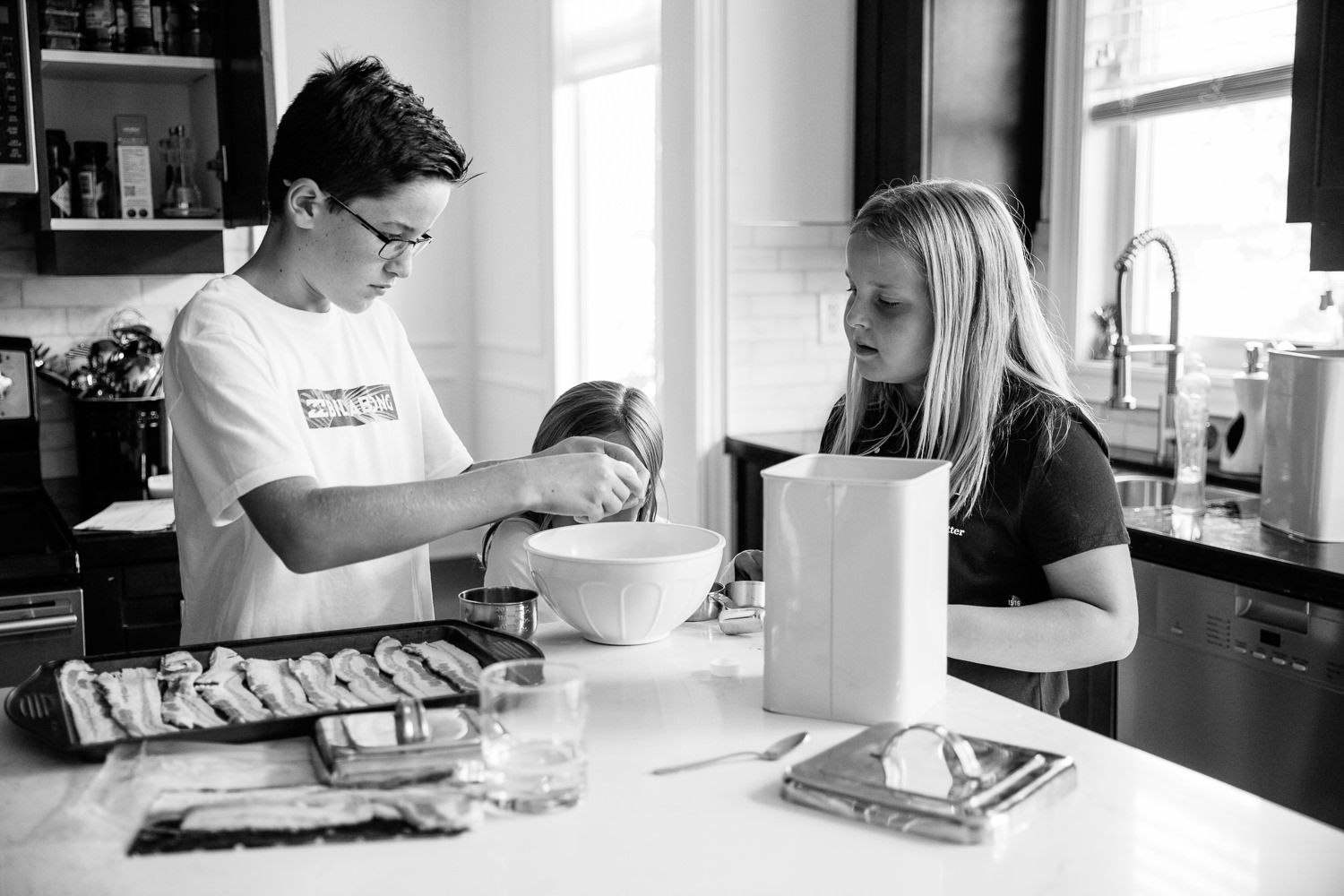 3 children standing at kitchen island mixing pancake batter for family brunch, 8 and 10 year old girls, 13 year old boy cracking eggs -Newmarket Lifestyle Photography