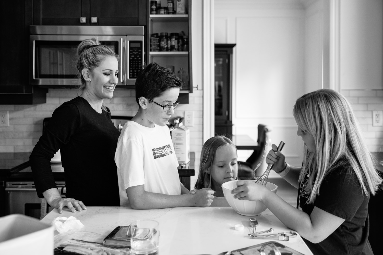 3 children standing at kitchen island mixing pancake batter for family brunch, 8 and 10 year old girls, mom standing behind 13 year old boy watching -Markham Lifestyle Photography