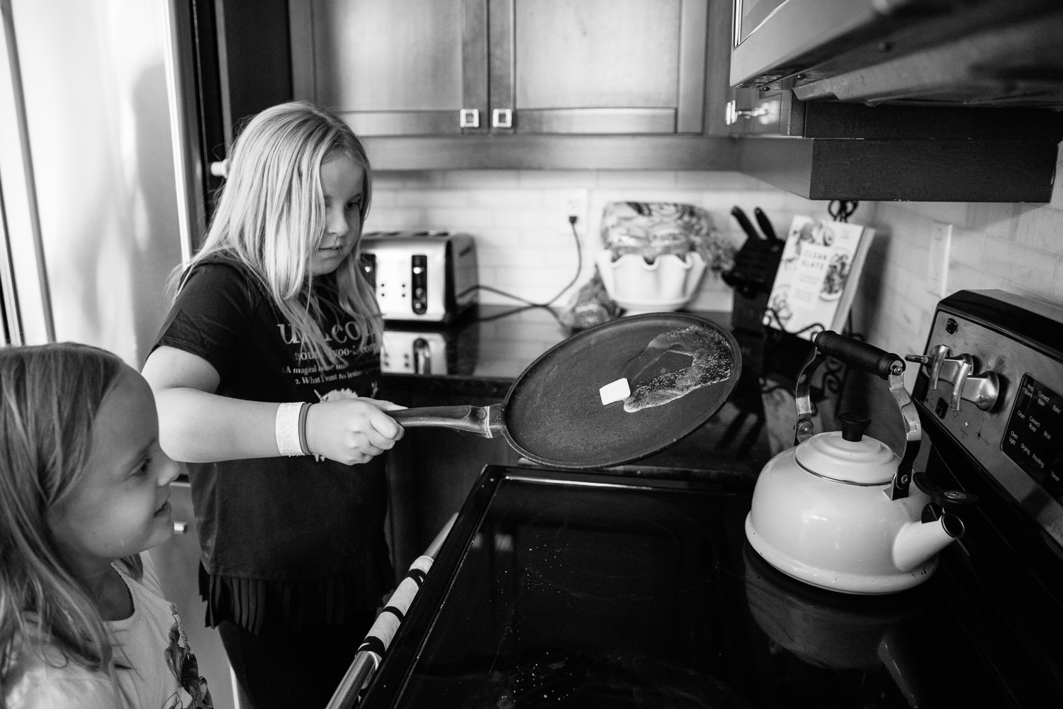 8 and 10 year old girls standing at stove, older sister melting butter across hot pan - Barrie Lifestyle Photography
