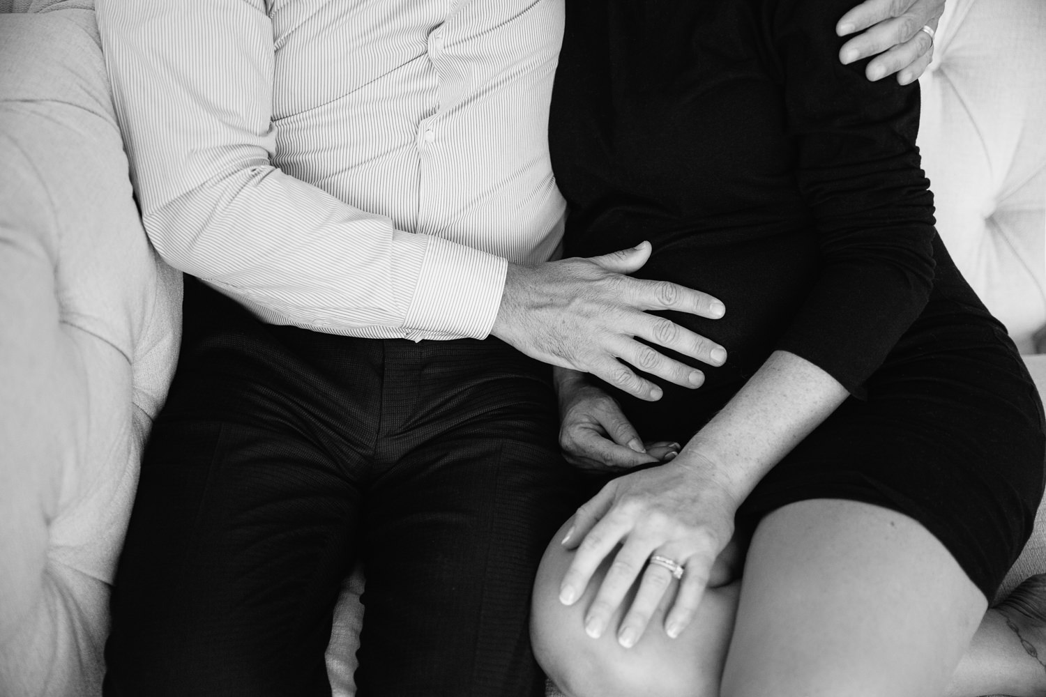 couple sitting together on couch, husband's hand on pregnant wife's belly, woman wearing black dress - Markham In-Home Photography