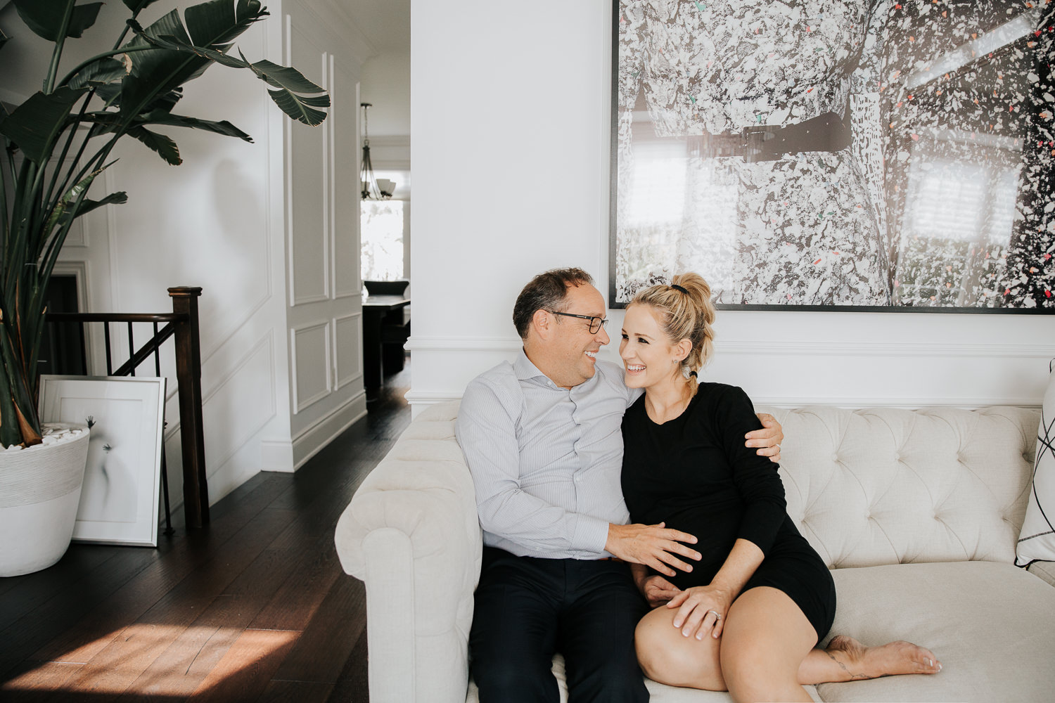 couple sitting together on couch smiling at one another, husband's hand on pregnant wife's belly, woman wearing black dress and blonde hair in braid - Stouffville In-Home Photography
