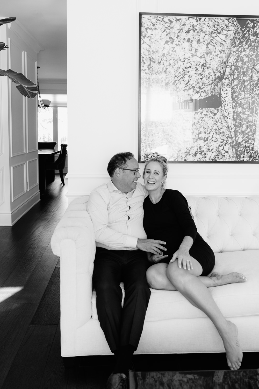 couple sitting together on couch smiling, husband's hand on pregnant wife's belly, woman wearing black dress and blonde hair in braid -Barrie In-Home Photography