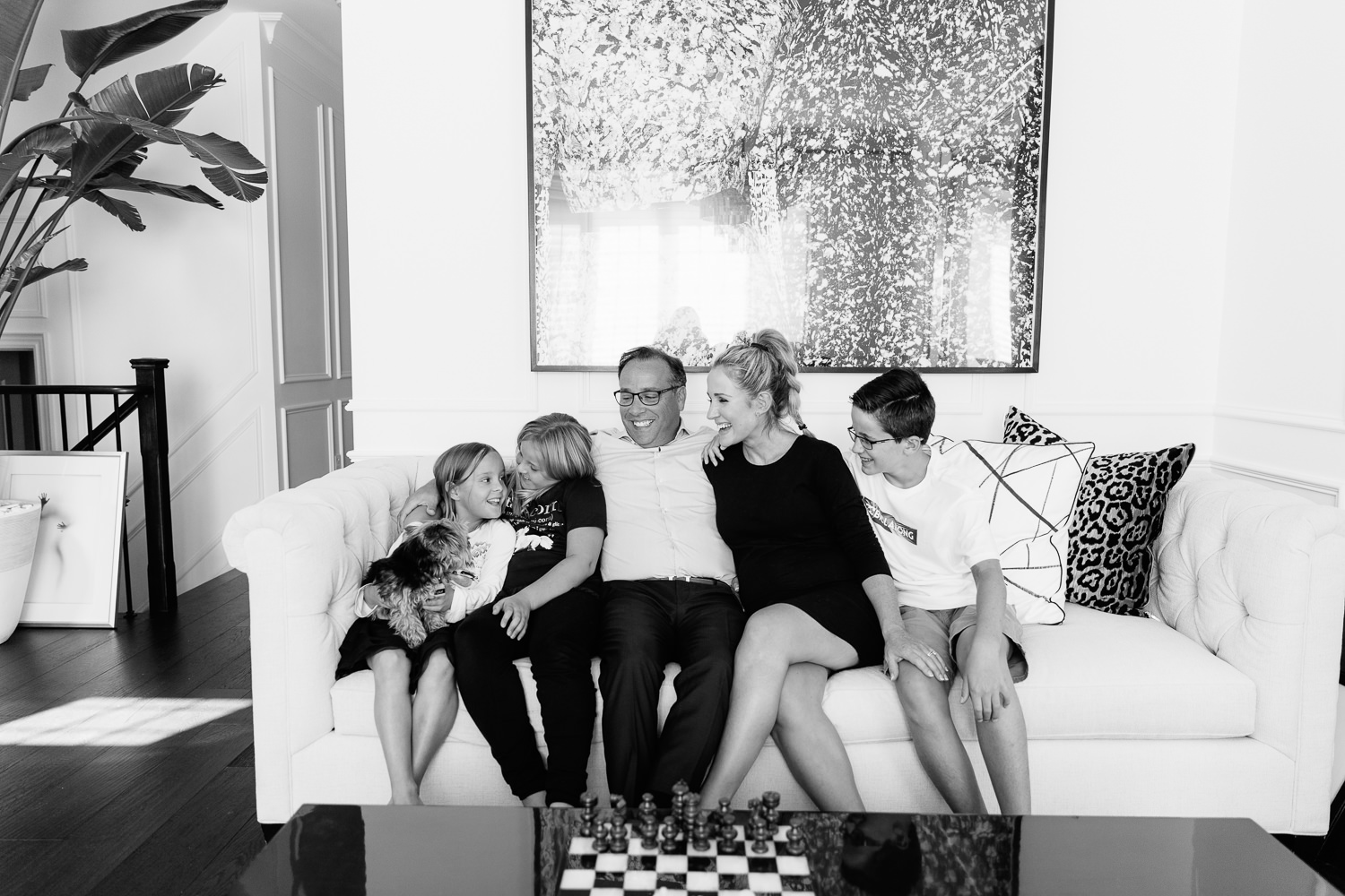 family of 5 sitting on couch together, smiling at one another, 2 daughters 1 son, 8 year old girl holding yorkie dog in lap - Newmarket In-Home Photos