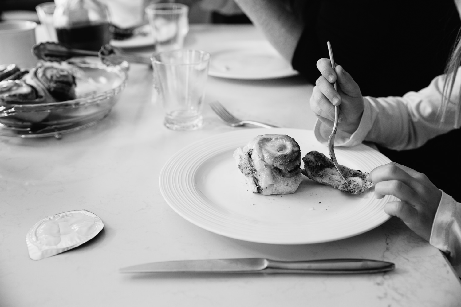 8 year old girl cutting up cinnamon bun while eating brunch with her family - GTA Lifestyle Photos