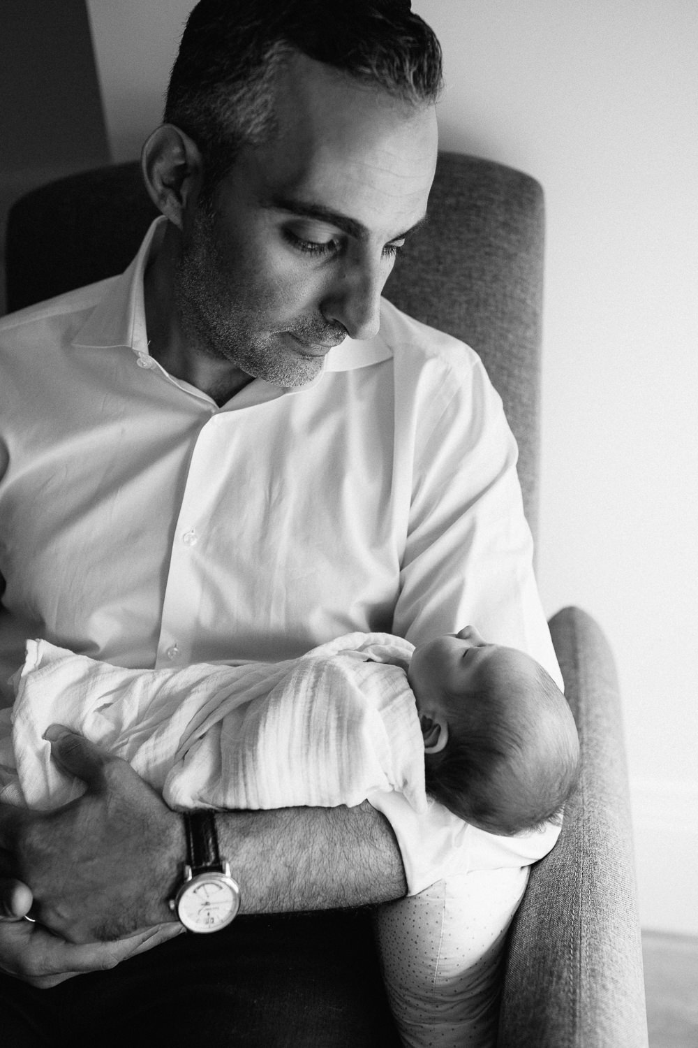 new dad sitting in nursery rocking chair, holding sleeping 2 week old baby boy in his arms, looking at son -Newmarket Lifestyle Photography