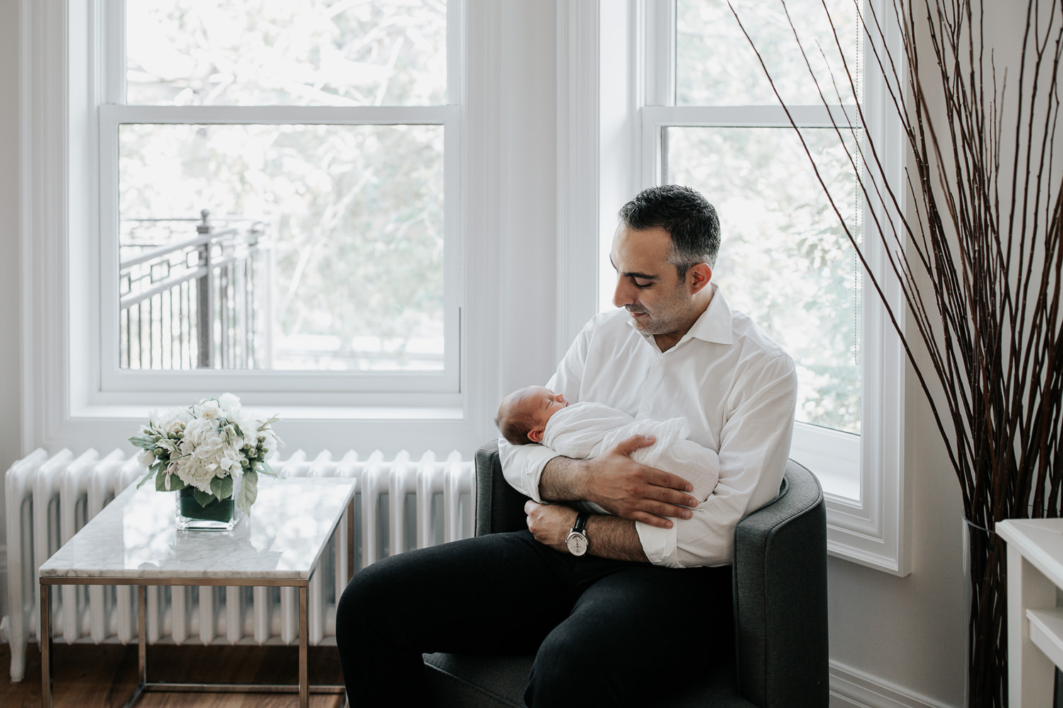 new father sitting in chair in living room, holding sleeping, swaddled 2 week old baby boy in his arms, smiling at son - Markham Lifestyle Photography