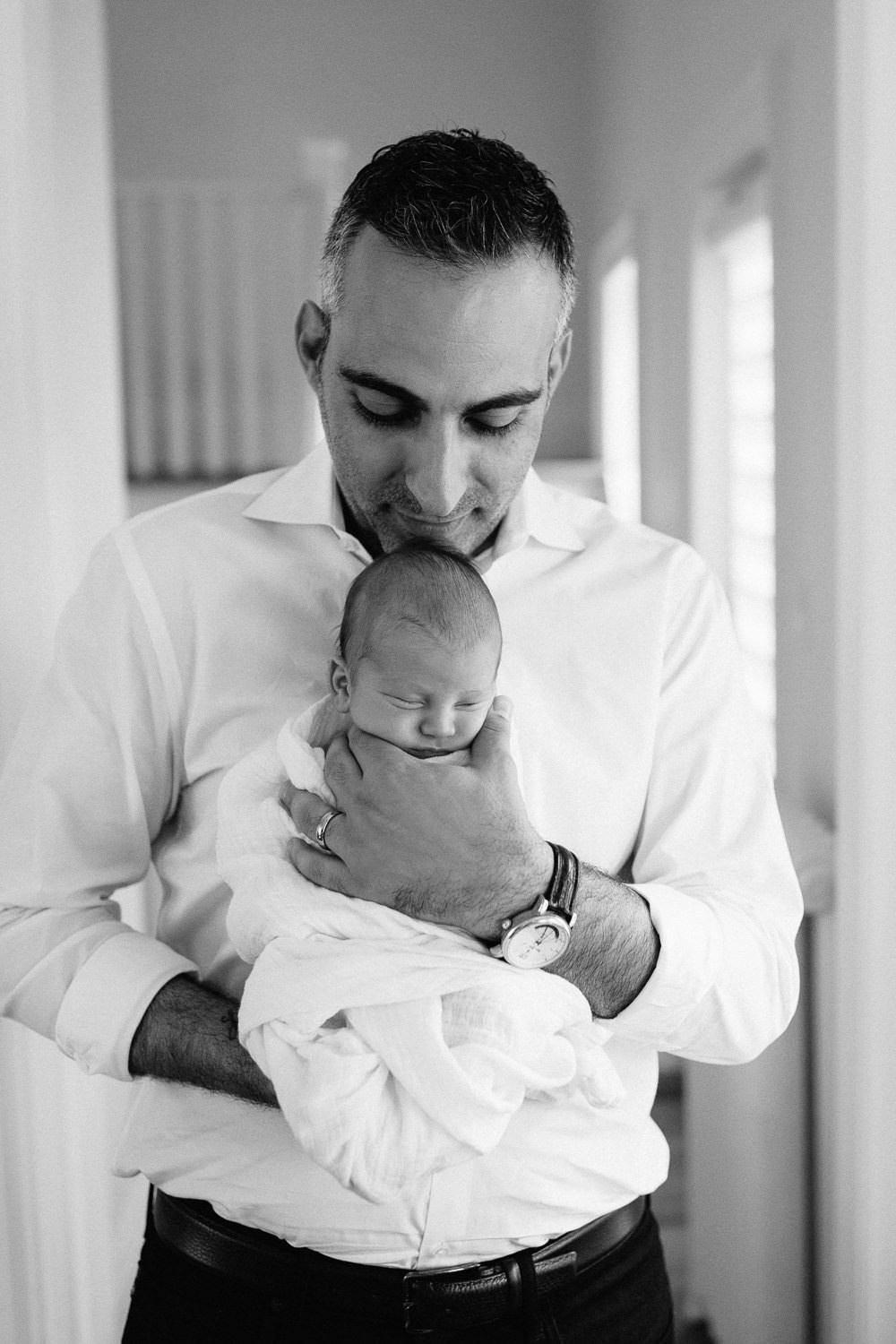 new father standing in living room, holding sleeping, swaddled 2 week old baby boy in his arms facing outward, smiling down at son -York Region Lifestyle Photography