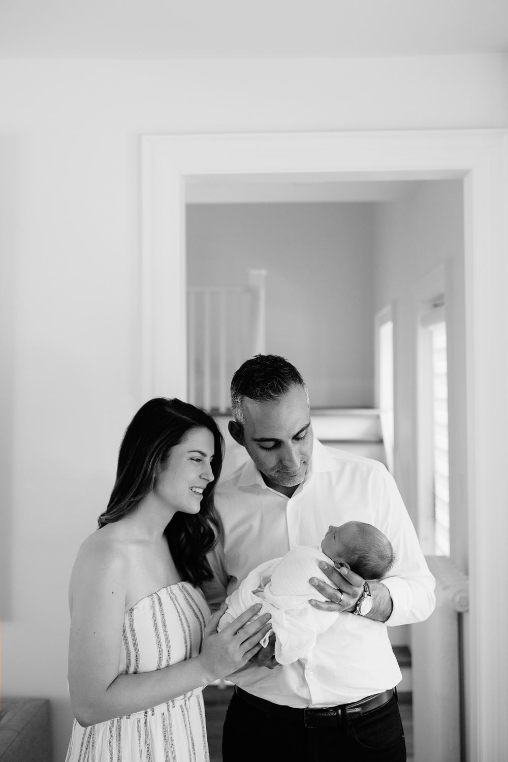new parents standing in living room, father holding sleeping, swaddled 2 week old baby boy in his arms, mother standing next to husband,smiling down at son -Newmarket In-Home Photography
