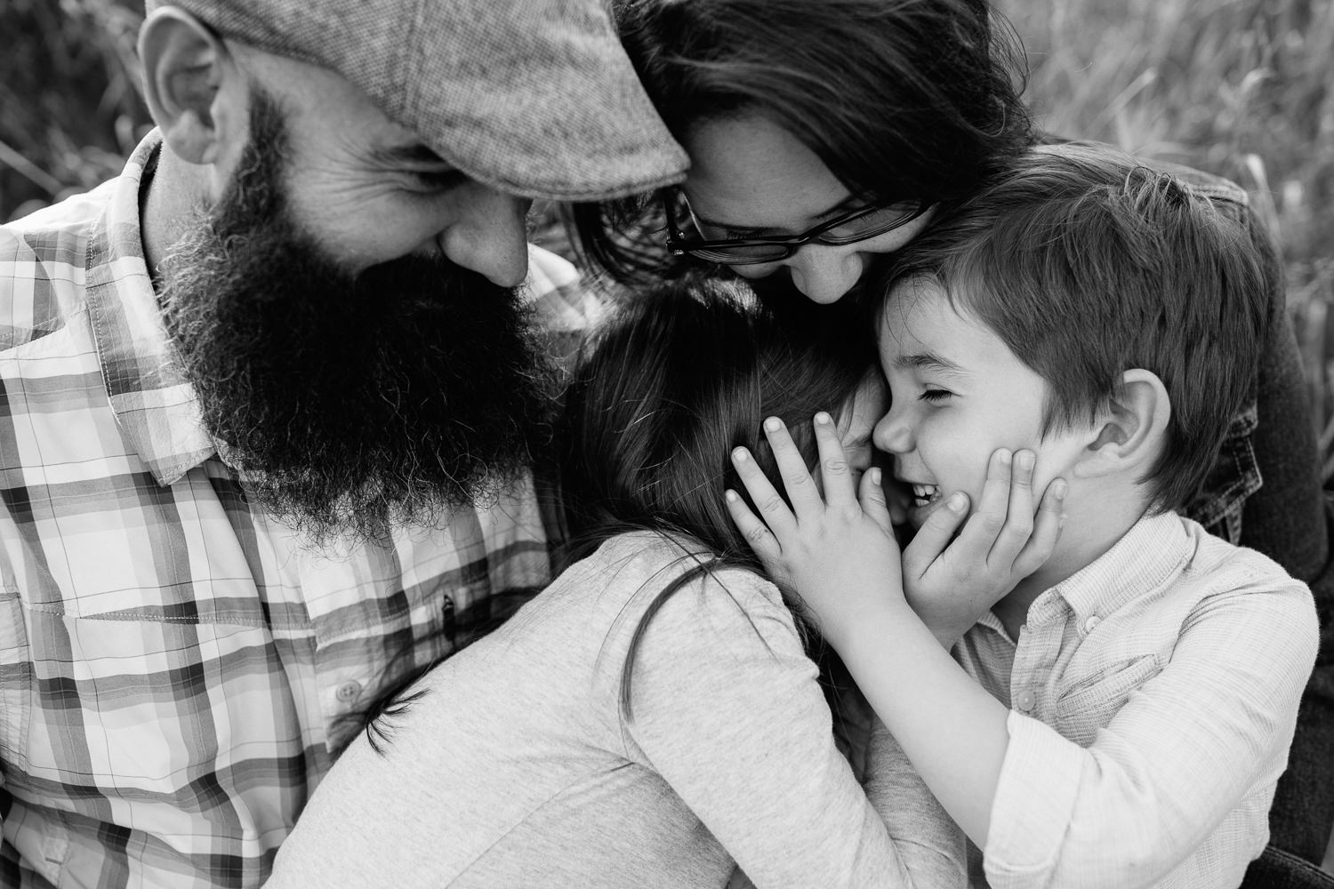 family of 4 sitting on park bench surrounded by tall grasses, 5 year old girl sitting on dad's lap, boy in mom's, snuggling, brother's hand on sister's face - Markham Lifestyle Photography