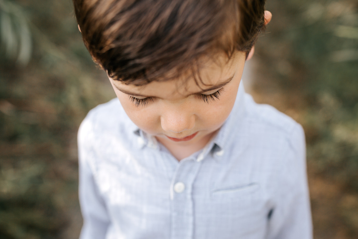 4 year old boy with dark hair and eyes wearing button down shirt standing on path looking down, close up of long eyelashes - Barrie In-Home Photos