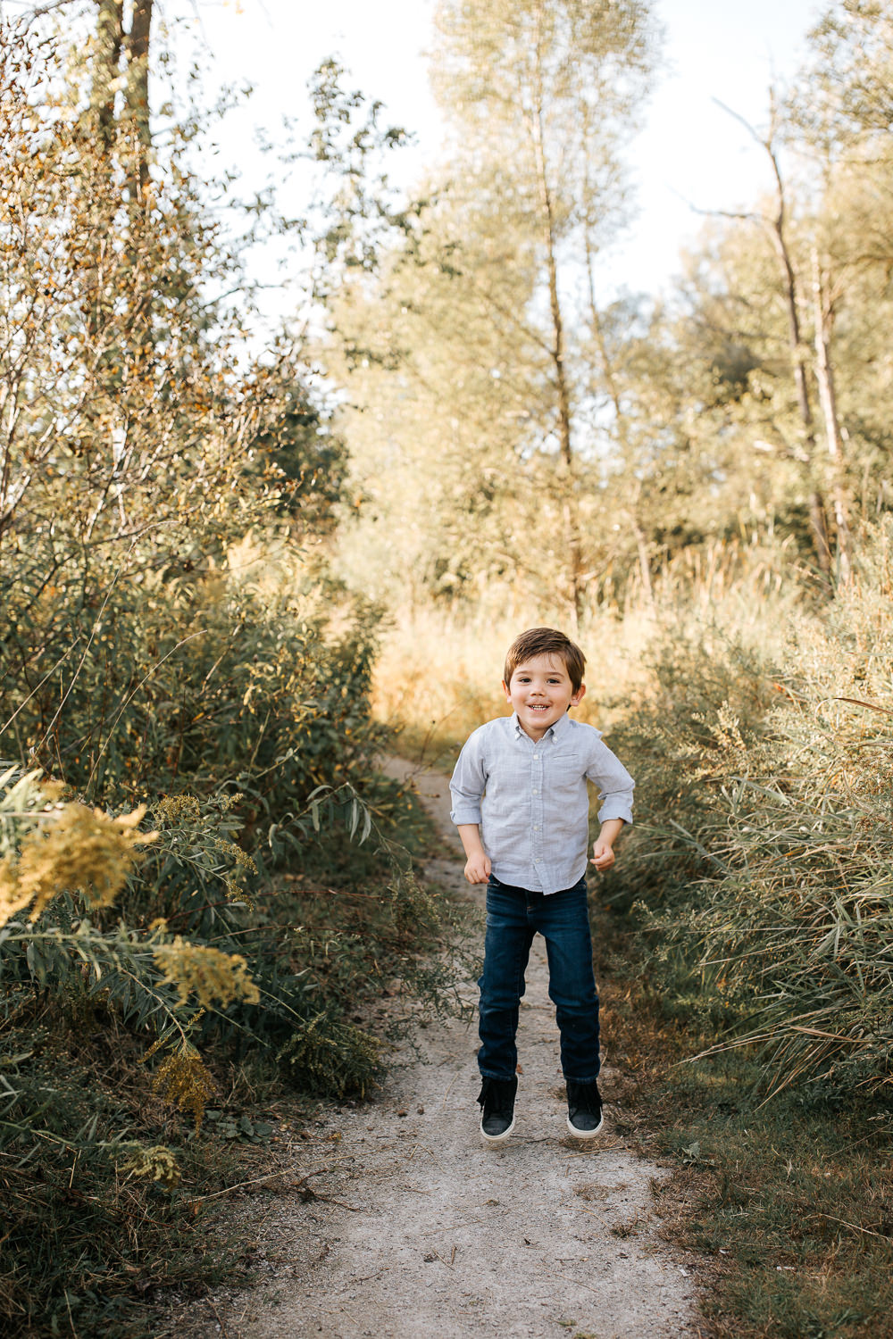 4 year old boy with dark hair and eyes wearing button down shirt jumping on path surrounded by tall grasses, looking at camera and smiling - GTA In-Home Photos