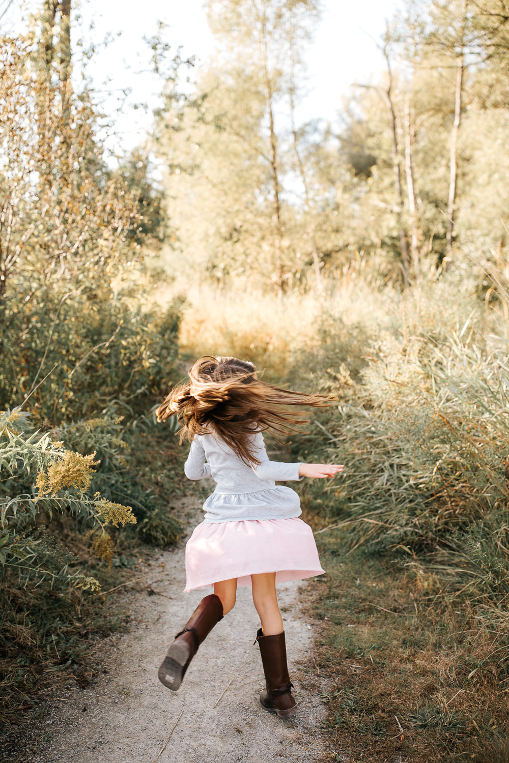 5 year old girl with long dark hair wearing tall boots and pink skirt twirling on path surrounded by tall grasses, hair and skirt moving - York Region In-Home Photos