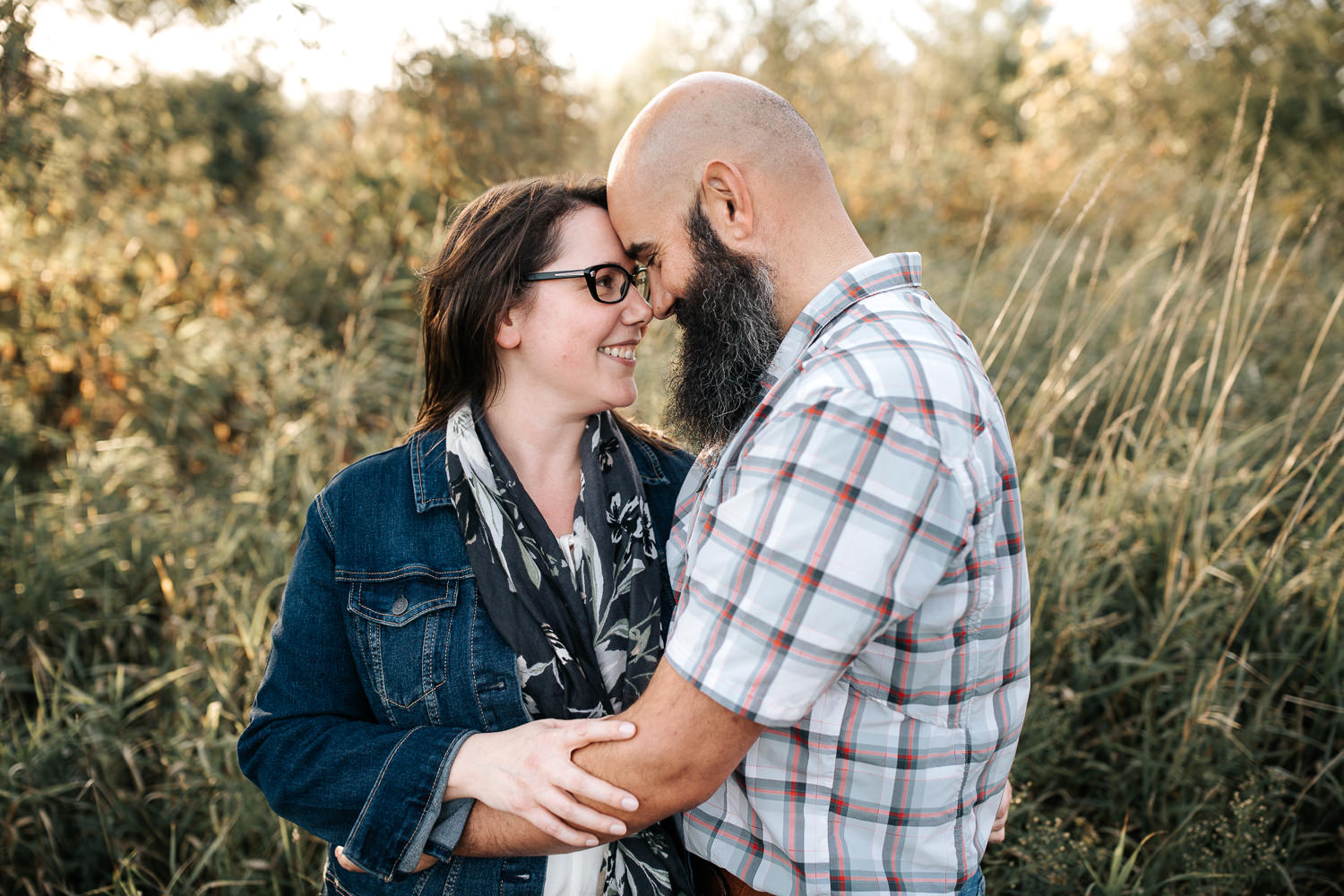 couple standing in grassy field at sunset, husband's arms around wife's waist, her hand on his arm, foreheads touching - Markham Lifestyle Photos