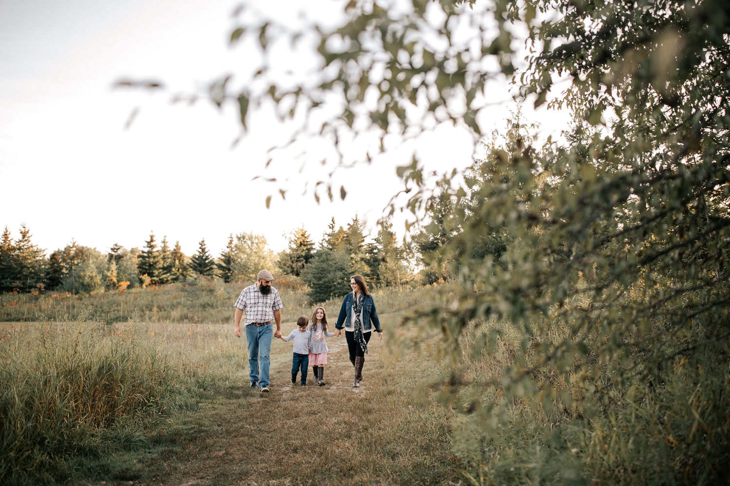 family of 4 holding hands, walking down path in grassy field, smiling at each other, trees in foreground - Barrie Lifestyle Photos