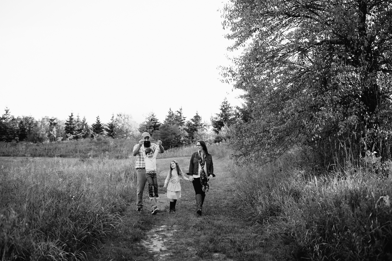 family of 4 holding hands, walking down path in grassy field, dad swinging son by both arms, mother and daughter smiling at them - GTA Lifestyle Photos