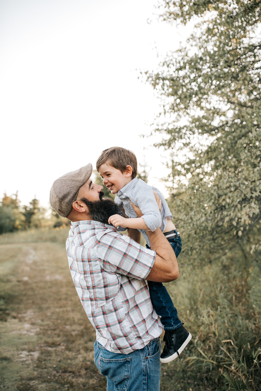 father standing in field holding 4 year old boy in his arms up in the air, face to face, son laughing and smiling at dad -Newmarket Lifestyle Photography
