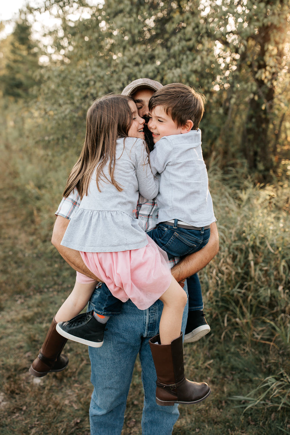 father standing in field holding 5 year old girl and 4 year old boy in his arms as daughter and son hug him, dad's face barely visible -Stouffville Lifestyle Photography