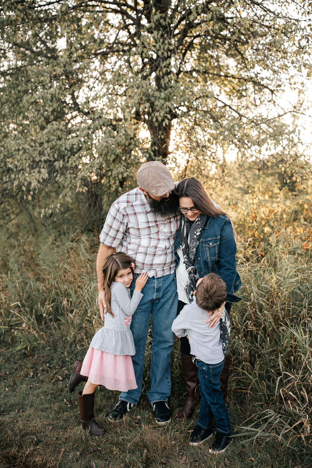 family of 4 standing together in grass field in front of tree, 5 year old girl hugging dad's leg, 4 year old boy looking up at mom, both parents looking at son -Barrie Lifestyle Photography