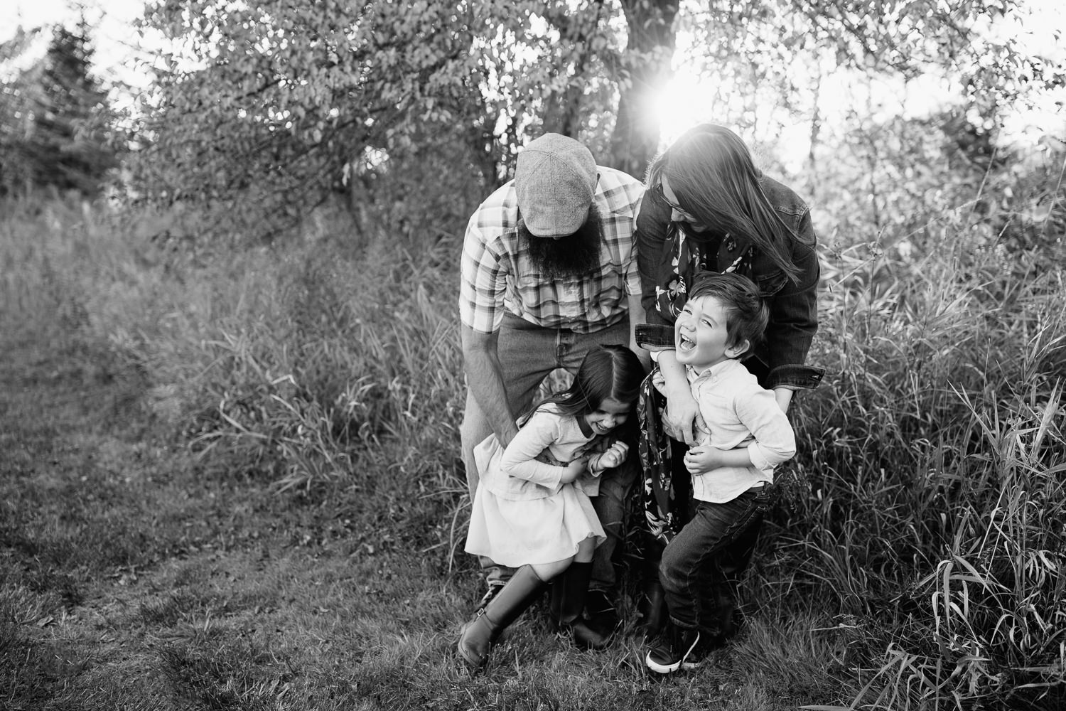 family of 4 standing togetherin grass field in front of tree, mom and dad leaning over, father tickling 5 year old daughter and mother tickling son, kids laughing - Newmarket In-Home Photography