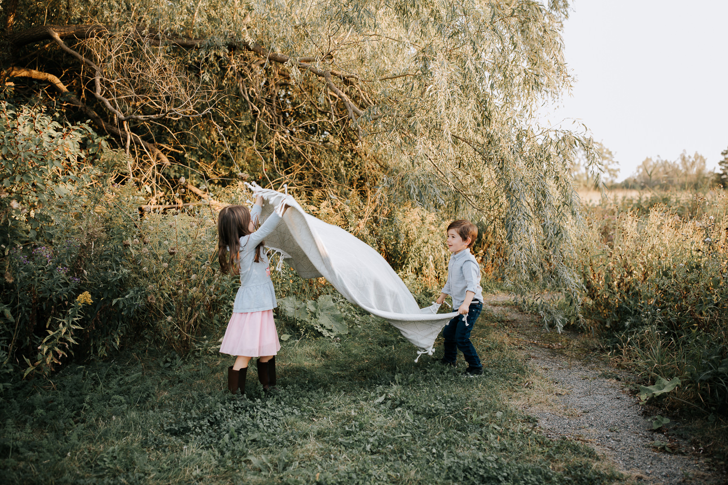 5 year old girl and 4 year old boy standing in front of tree spreading white picnic blanket on the grass - Barrie In-Home Photography