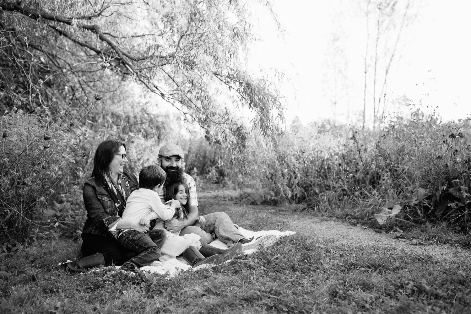 family of four sitting on blanket under willow tree, 4 year old boy sitting in mom's lap and leaning over to tickle big sister in dad's lap as she laughs -  GTA In-Home Photography