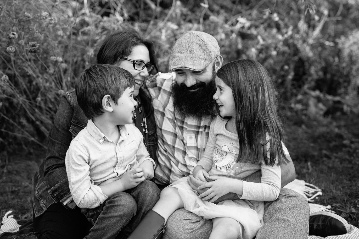 family of four sitting on blanket under willow tree, 4 year old boy sitting in mom's lap, 5 year old girl sitting in dad's lap, looking at one another and smiling - Newmarket In-Home Photos