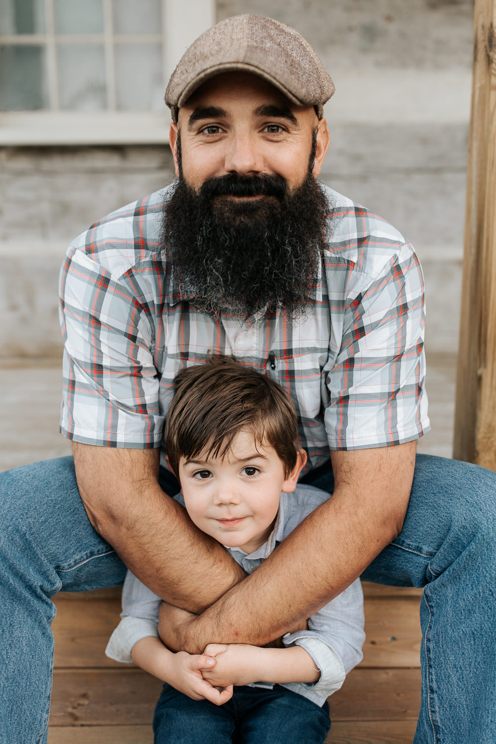 father sitting on wood porch step with 4 year old boy on the step below, dad's arms wrapped around son, both smiling at camera -Markham In-Home Photos