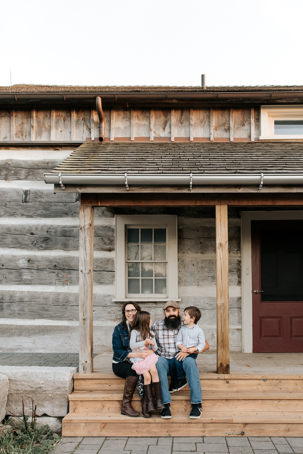 family of four sitting on porch of log cabin, mom and dad looking at camera as 4 year son and 5 year old daughter sit in their laps smiling at one another -York Region In-Home Photos