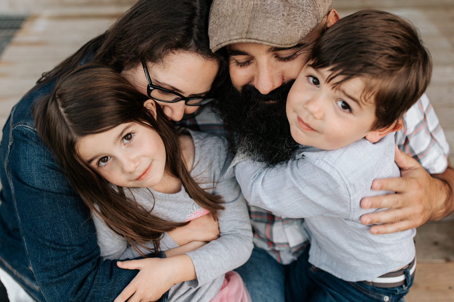 family of foursitting on porch, 4 year boy sitting in dad's lap and 5 year old girl in mom's, snuggled up together in an family hug, son and daughter looking up at camera - Newmarket Lifestyle Photos