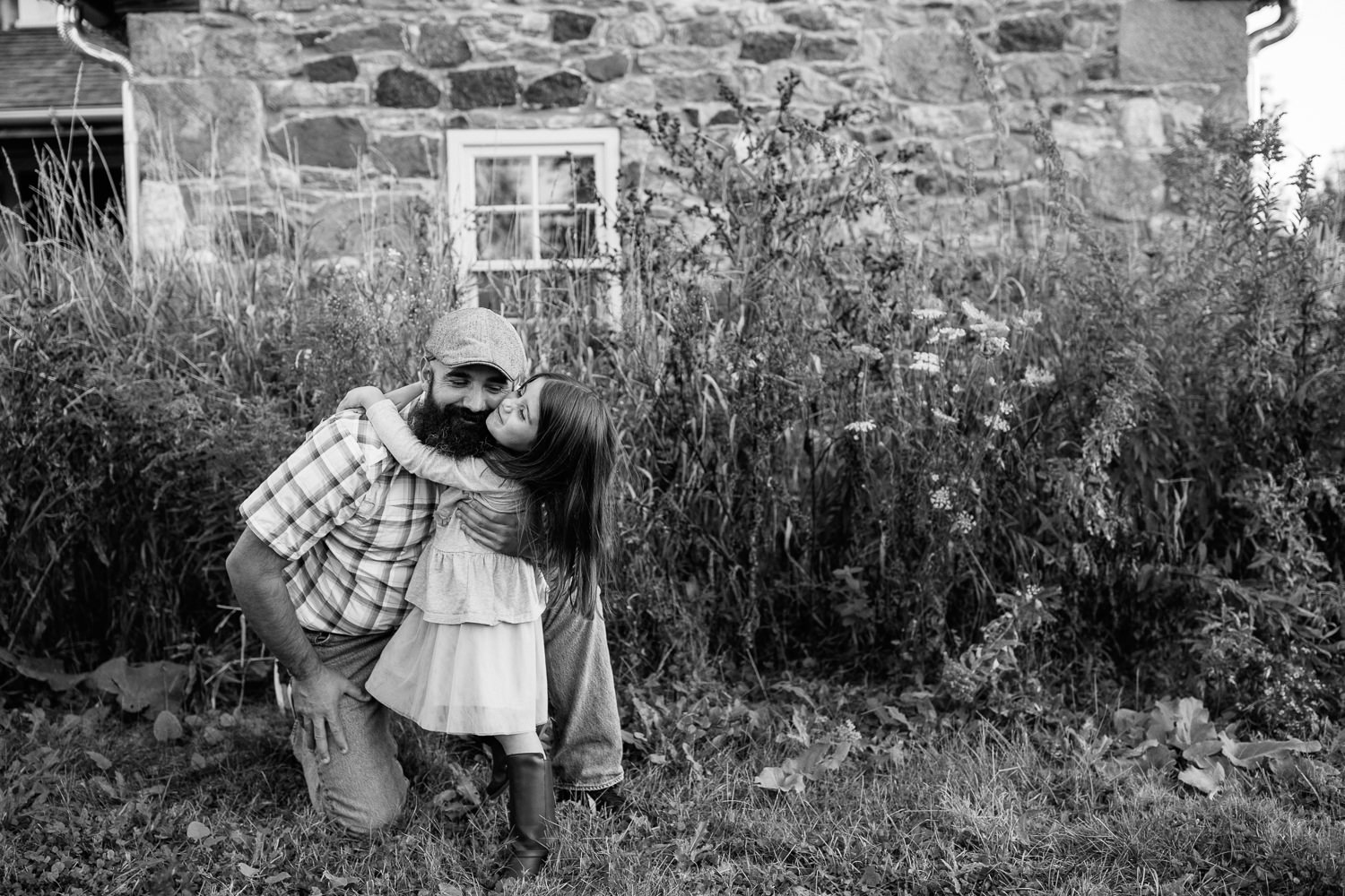 father bending down on one knee in front of old stone house as 5 year old girl hugs him around the neck, dad's arm around daughter - Stouffville Lifestyle Photos