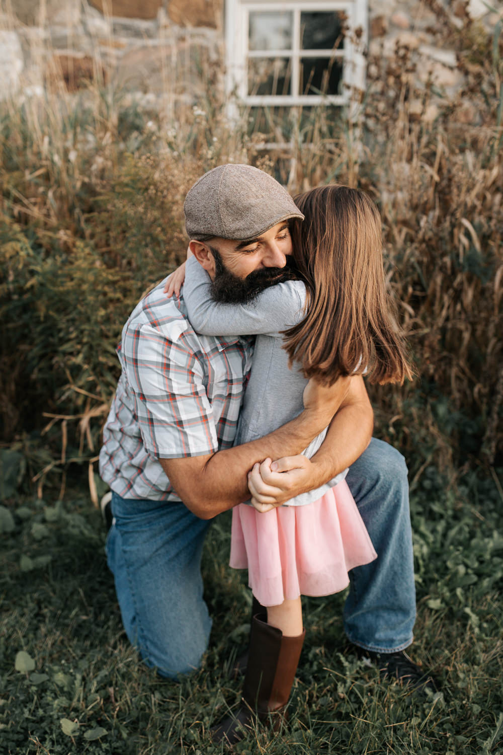 father bending down on one knee in front of old stone house as 5 year old girl hugs him around the neck, dad's arms around daughter, eyes closed and smiling -Barrie Lifestyle Photos