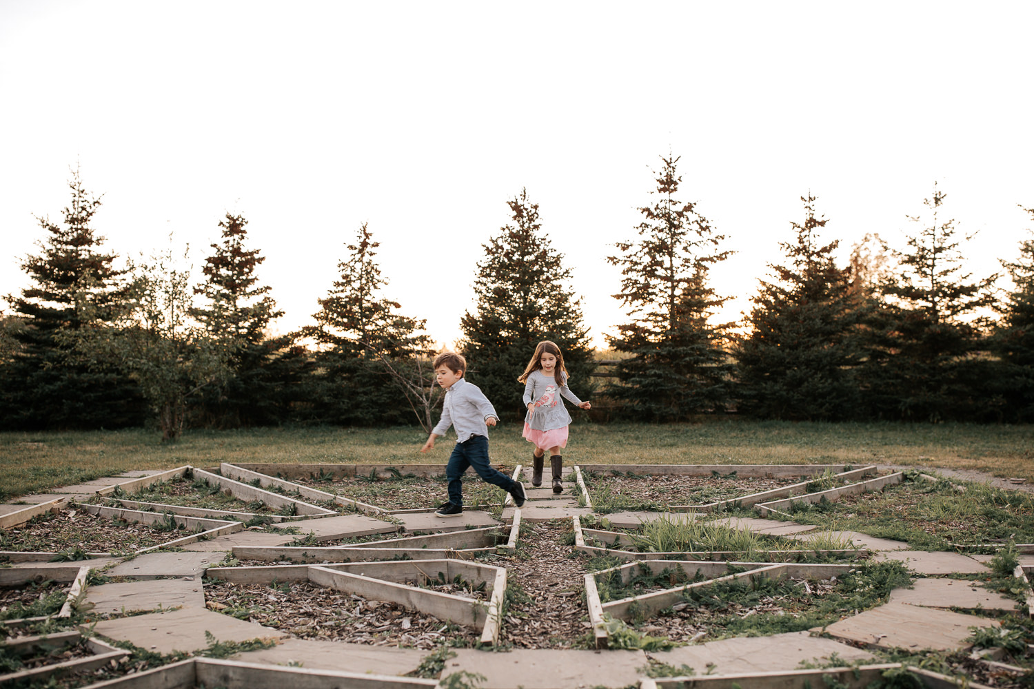 4 year old boy and 5 year old girl both with dark hair running through maze on ground as sun sets behind them - York Region Lifestyle Photos