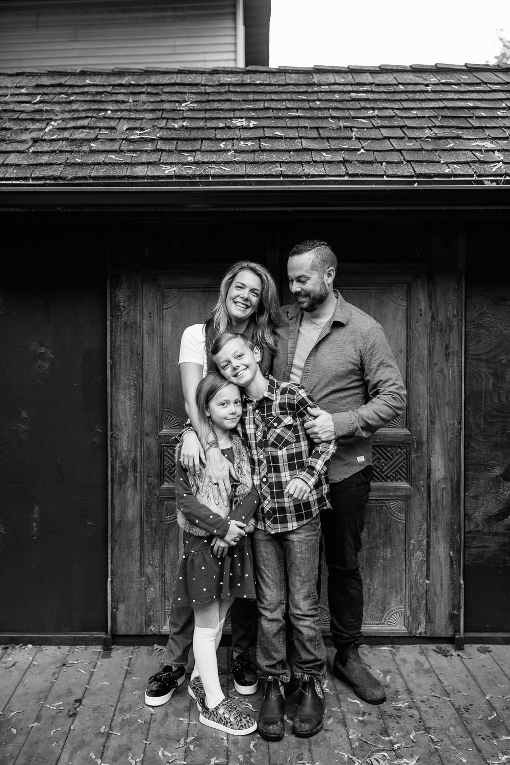 family of 4 standing on front of dark home with old doors, mom's arms around 7 year old girl's shoulders, 9 year old boy hugging sister, dad's hand on son smiling at him - Stouffville Lifestyle Photography