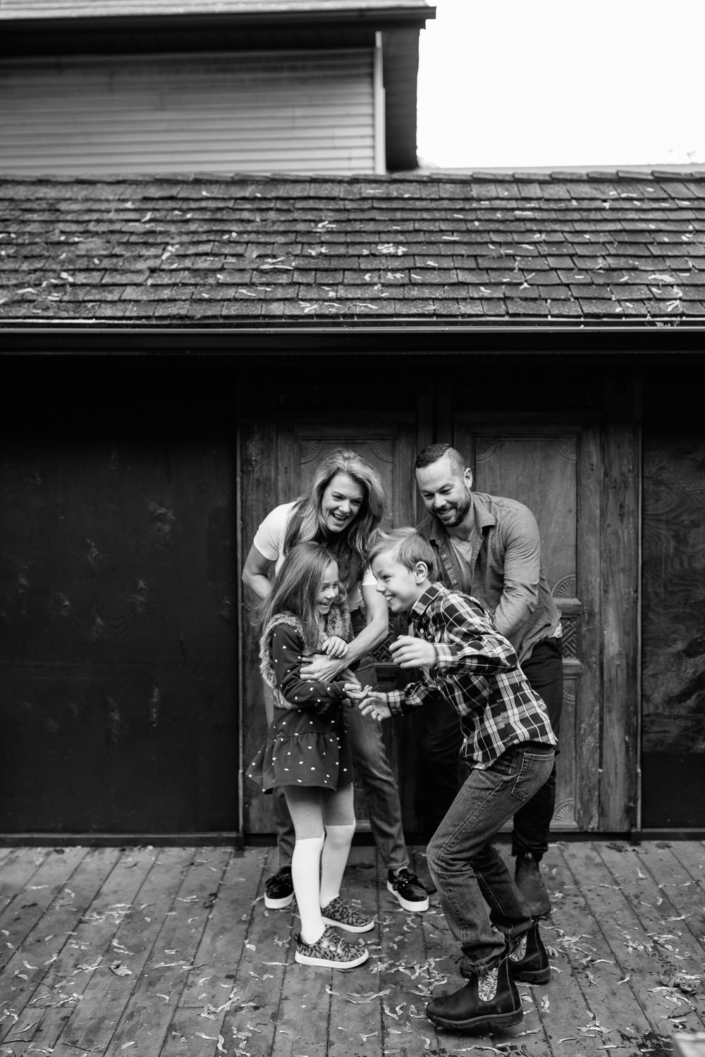 family of 4 standing on front of dark coloured home with old doors, mom and and dad tickling 7 year old girl and 9 year old boy as kids try to get away, laughing -Markham Lifestyle Photography