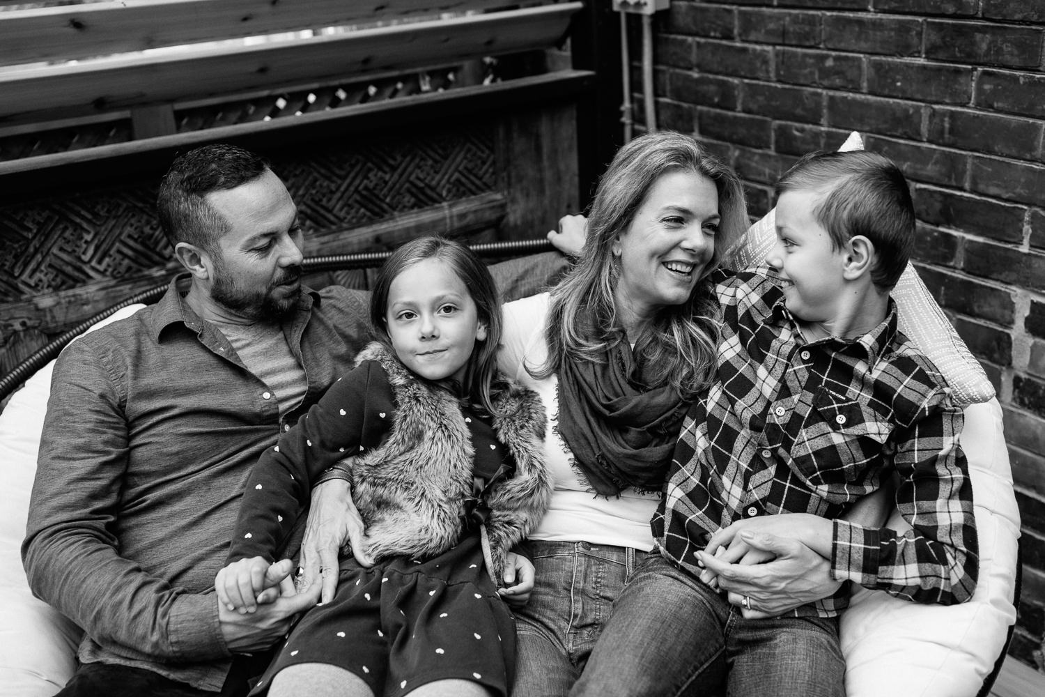 family of 4 sitting and snuggling on outdoor couch, 7 year old girl sitting in dad's lap holding his hand, 9 year old boy sitting in mom's lap smiling at her - GTA Lifestyle Photography