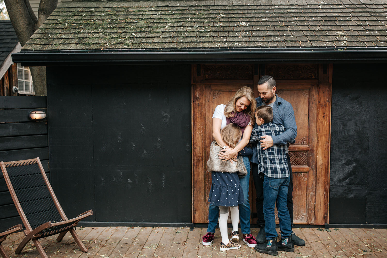 family of 4 standing on front of dark home with old doors, 7 year old girl hugging mother, 9 year old boy hugging father - Barrie Lifestyle Photography