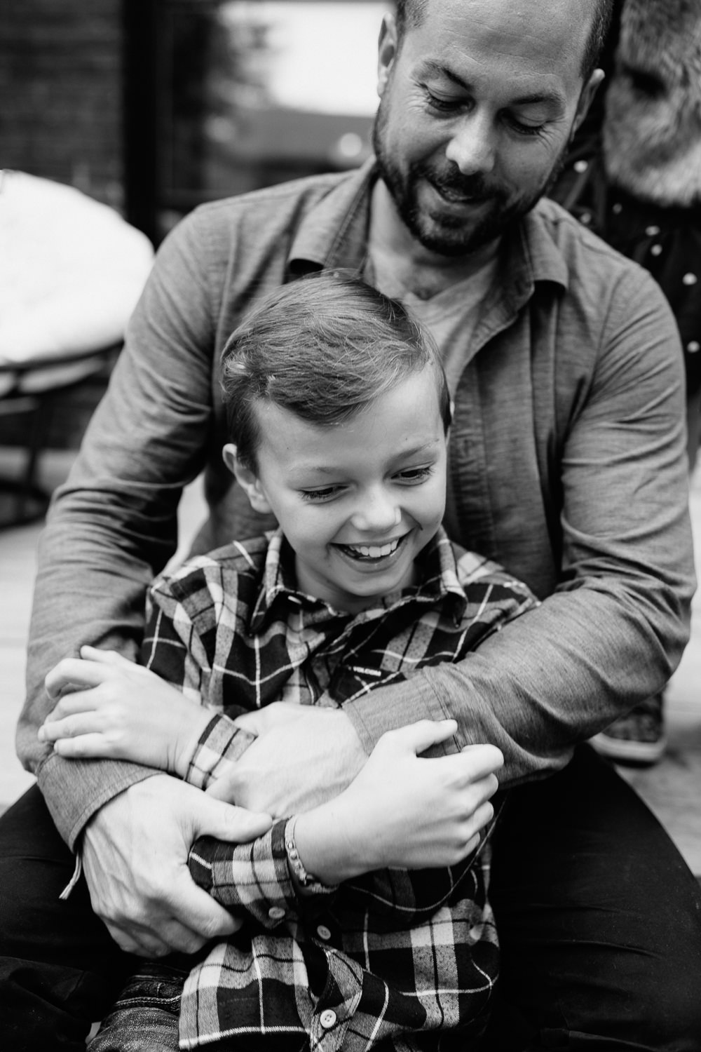 9 year old boy sitting between dad's legs as they sit on backyard porch step, dad's arms around son as he tries to escape, both laughing - Markham In-Home Photography