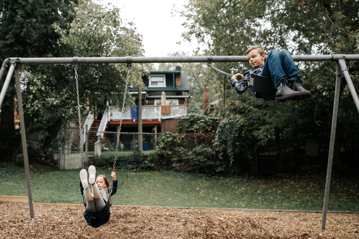 9 year old boy and 7 year old girl at outdoor park in the city swinging on swing set, brother swinging high in air and looking to the side - GTA In-Home Photography