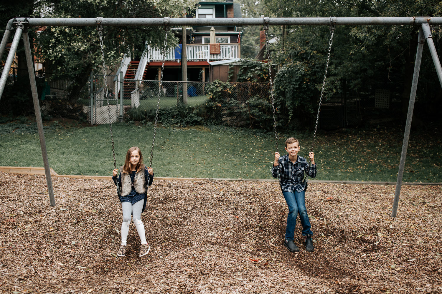 7 year old girl and 9 year old boy sitting still on swing set at city park, both looking  and smiling at the camera -  Stouffville In-Home Photos