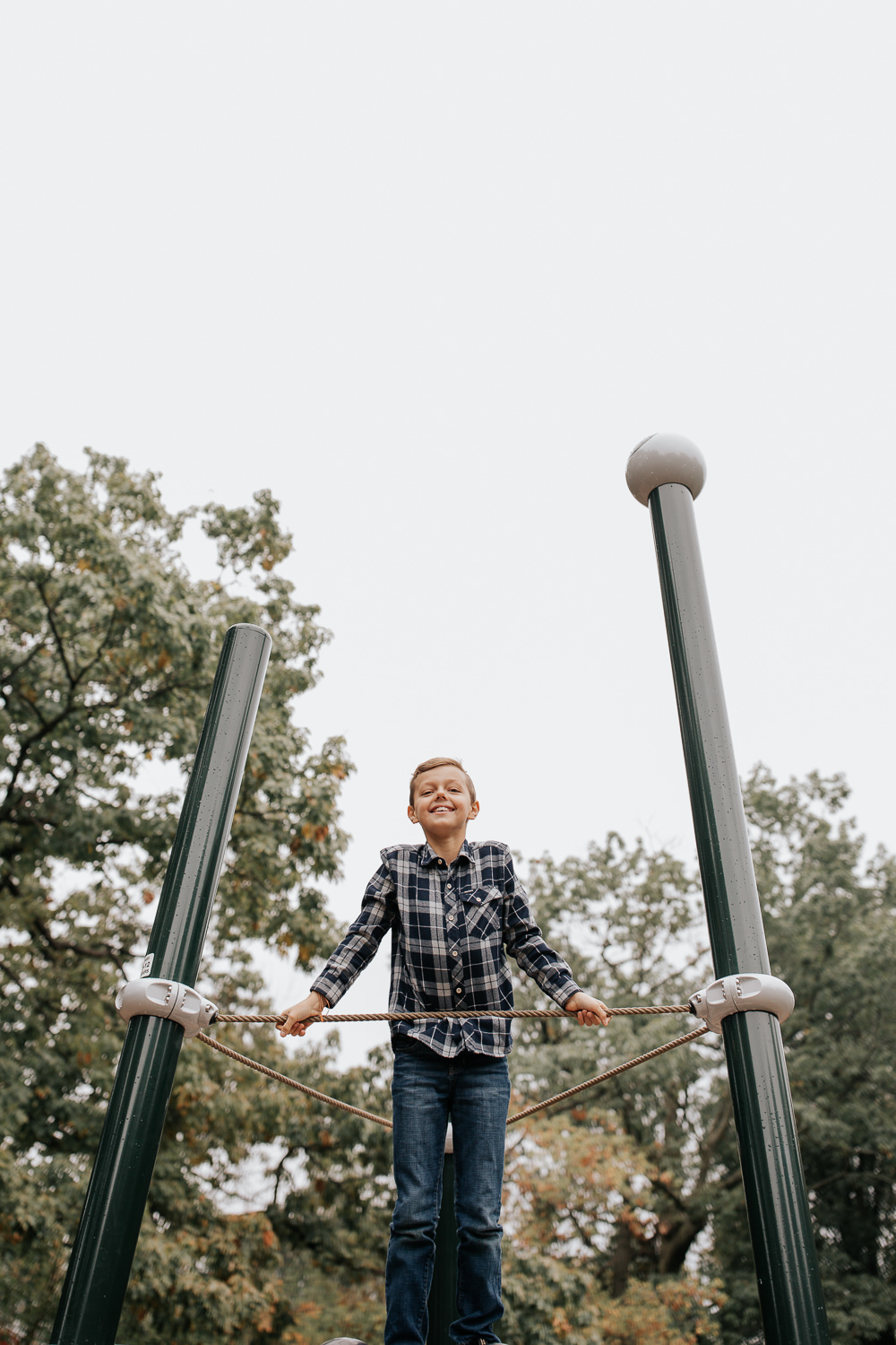 9 year old boy in plaid shirt with light brown hair standing on top of jungle gym at park and smiling down at camera - GTA Lifestyle Photos
