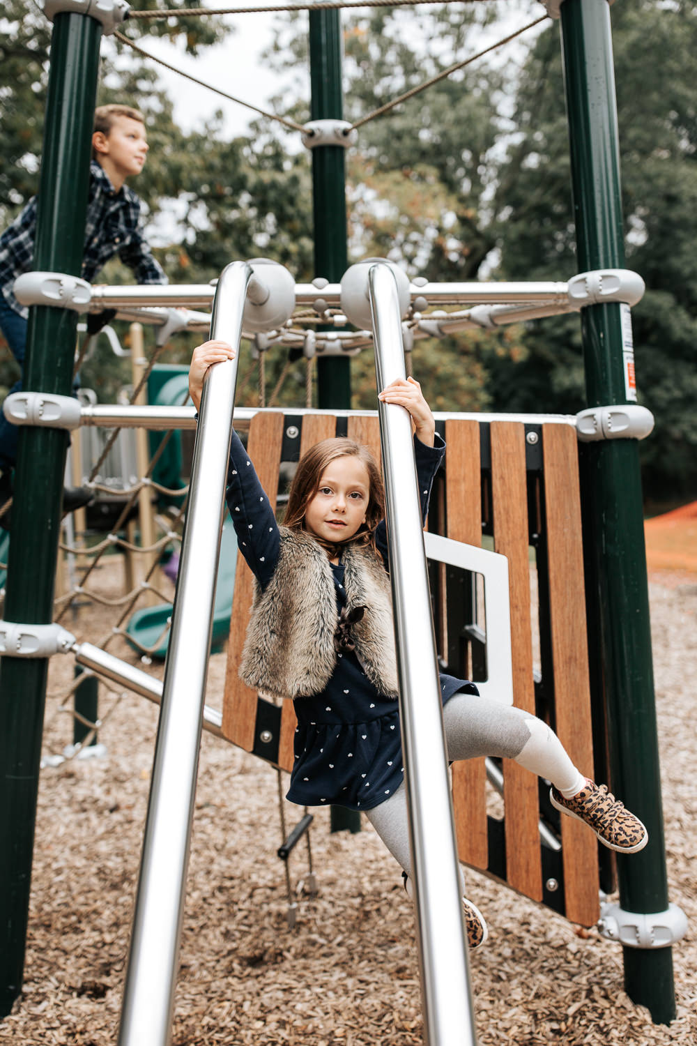 7 year old girl with light brown hair in dress and fur vest swinging from jungle gym at park, and looking seriously at camera -York Region Lifestyle Photos