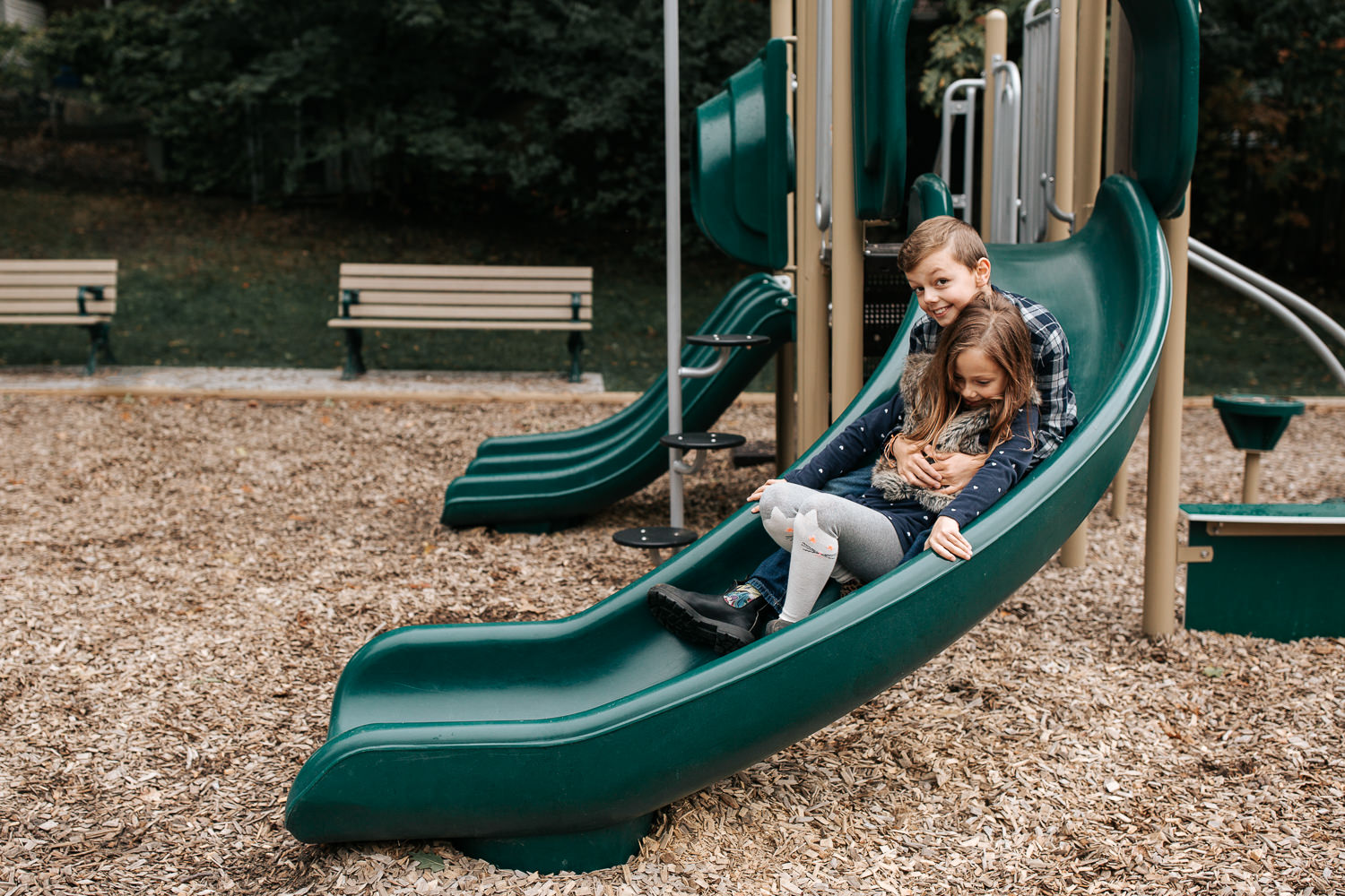 7 year old girl and 9 year old boy going down park slide, big brother sitting behind sister as they slide down - Barrie Lifestyle Photos