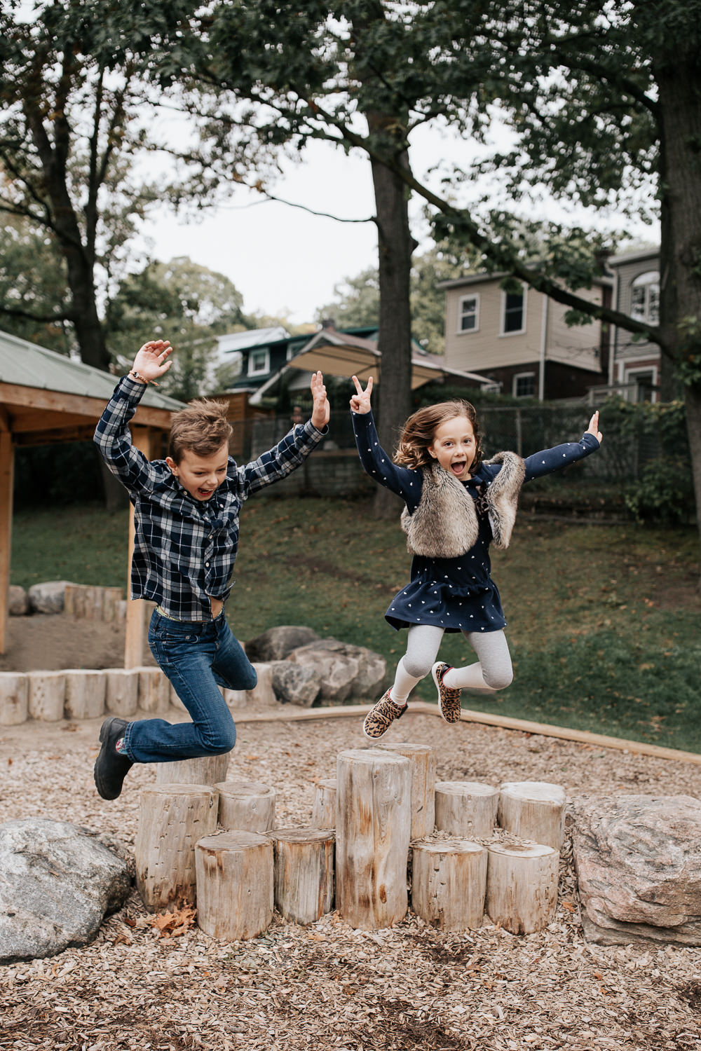 7 year old girl and 9 year old boy jumping off tree stumps at park, arms in air, mouths open, smiling, little sister looking at camera -York Region Lifestyle Photos