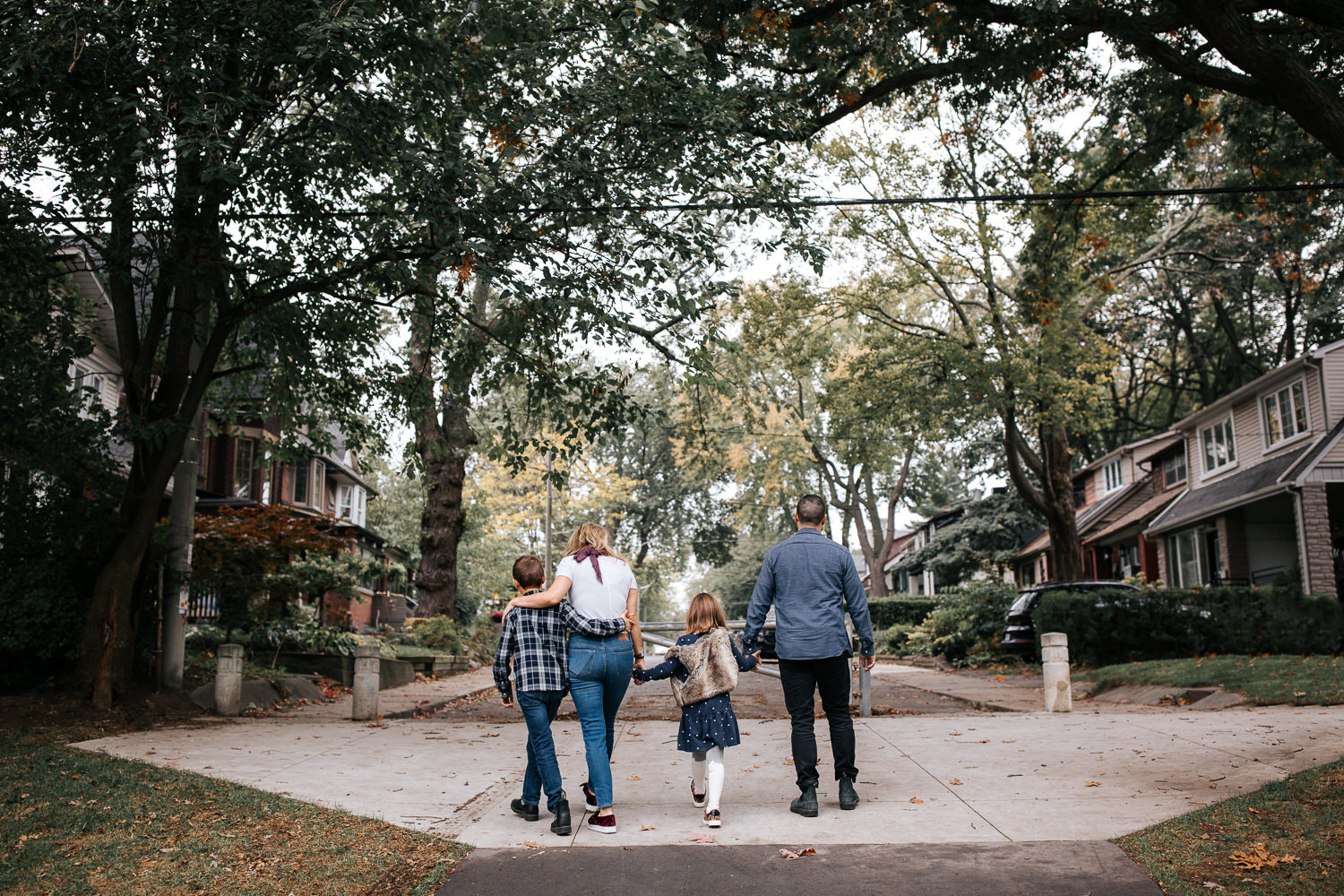 family of 4 walking out of city park towards their home, mom with arm around 9 year old boy, 7 year old girl holding hands with mother and father - Stouffville Lifestyle Photos