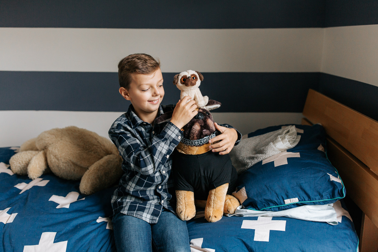 9 year old boy in plaid shirt with light brown hair sitting on bed in blue and white room holding toy pug stuffed animals, smiling at them - Markham In-Home Photography